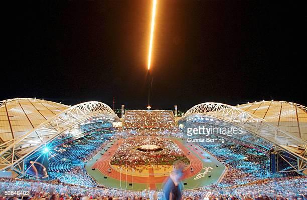"""Sydney; Ein Jet ueberfliegt das Olympiastadion in Sydney und """"pustet"""" die Olympische Flamme aus"""