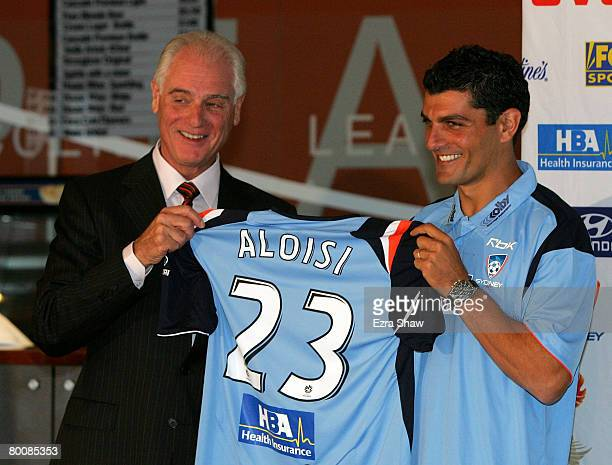 Sydney FC Chairman Andrew Kemeny holds up a jersey with John Aloisi during a press conference announcing that Aloisi has signed with Sydney FC at the...
