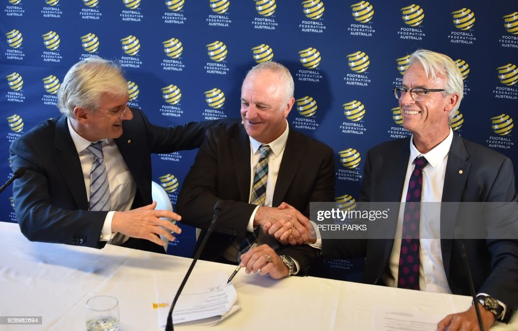 Sydney FC coach Graham Arnold (C) shakes hands with Football Federation Australia Chief Executive Officer David Gallop (R) and chairman Steven Lowy (L) after he was announced Australia soccer team coach at a press conference in Sydney on March 8, 2018. Arnold will take over as Australia coach after the World Cup 2018, replacing Dutchman Bert van Marwijk who was hired on a short-term basis to guide the team in Russia, football officials announced. /