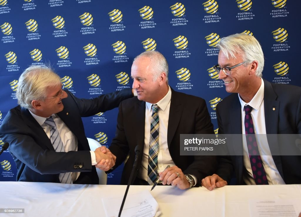 Sydney FC coach Graham Arnold (C) shakes hands with Football Federation Australia chairman Steven Lowy (L) and Chief Executive Officer David Gallop (R) after he was announced Australia soccer team coach at a press conference in Sydney on March 8, 2018. Arnold will take over as Australia coach after the World Cup 2018, replacing Dutchman Bert van Marwijk who was hired on a short-term basis to guide the team in Russia, football officials announced. /