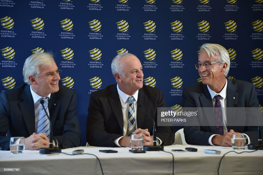 Sydney FC coach Graham Arnold (C) smiles at a press conference with Football Federation Australia chairman Steven Lowy (L) and Chief Executive Officer David Gallop (R) after he was announced Australia soccer team coach in Sydney on March 8, 2018. Arnold will take over as Australia coach after the World Cup 2018, replacing Dutchman Bert van Marwijk who was hired on a short-term basis to guide the team in Russia, football officials announced. /