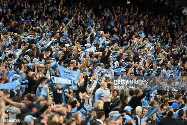 Sydney FC fans celebrate their team's first goal against Melbourne Victory during the 2017 ALeague Grand Final football match at Allianz Stadium in...