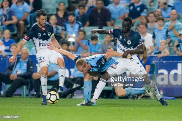 Sydney FC forward Matt Simon battles for the ball with Melbourne Victory defender Thomas Deng and Melbourne Victory midfielder Carl Valeri at the...