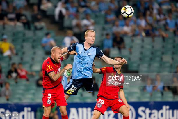Sydney FC forward Matt Simon rises above Adelaide United defender Taylor Regan to head towards goal at the ALeague Soccer Match between Sydney FC and...