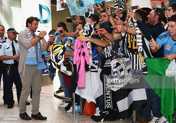 Sydney FC's Italian footballer Alessandro Del Piero signs autographs as he arrives at Sydney International Airport on September 16 2012 in Sydney...