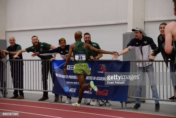Sydney Gidabuday of Adams State runs past fans after winning the Men 3000 Meter Run at The Division II Men's and Women's Indoor Track Field...