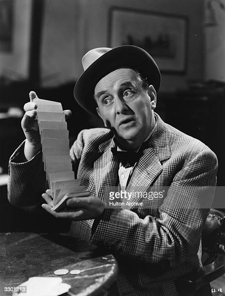 Sydney Howard the comedian demonstrates his playing card skills in a scene from 'Shipyard Sally', directed by Monty Banks for 20th Century Fox.