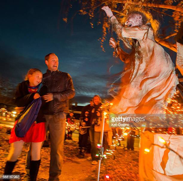 Sydney Lenssen, left, dressed as Superwoman for Halloween is frightened along with her father Kevin as they and other Trick or Treaters visit a house...
