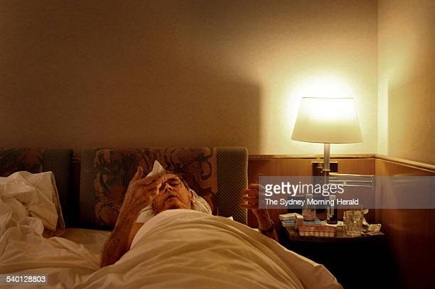 Sydney man Dr John Elliott inspects where his hands have started to bleed wracked with pain as he attempts to rise from his hotel room bed in Zurich...