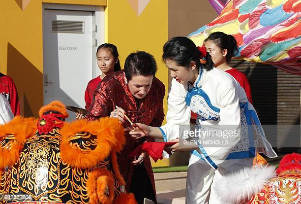 Sydney mayor Clover Moore dots the eyes of a lion dance troupe to open the Lunar New Year celebrations in Sydney on January 27 2017 Much of the...