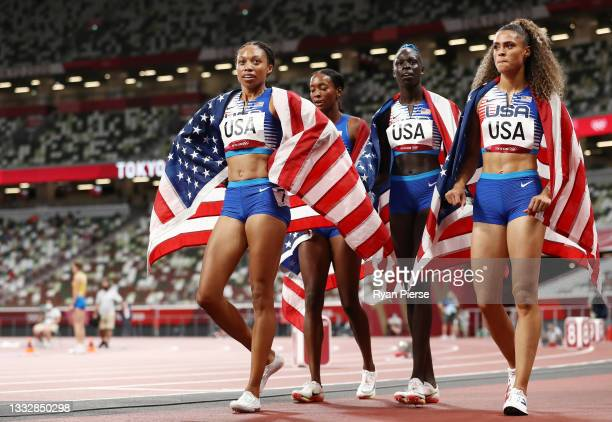 Sydney McLaughlin, Allyson Felix, Dalilah Muhammad and Athing Mu of Team United States celebrate winning the gold medal in the Women' s 4 x 400m...