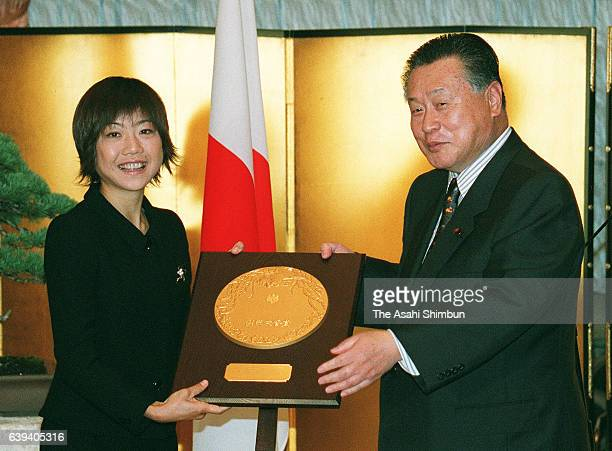 Sydney Olympic women's marathon gold medalist Naoko Takahashi receives the shield from Japanese Prime Minister Yoshiro Mori during the People's...