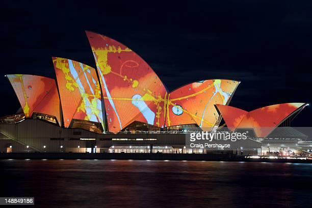 Sydney Opera House colourfully illuminated at night during 'Vivid' festival.