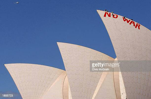 """Sydney Opera House staff scrub off the """"No War"""" graffiti painted in blood red letters by anti war protesters on the tip of the tallest sail of the..."""