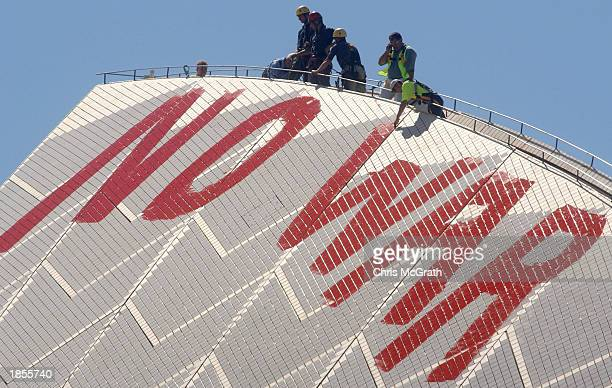 """Sydney Opera House staff scrub off the """"No War"""" graffiti painted in blood red letters by anti war protesters on the tip of the tallest sail on March..."""