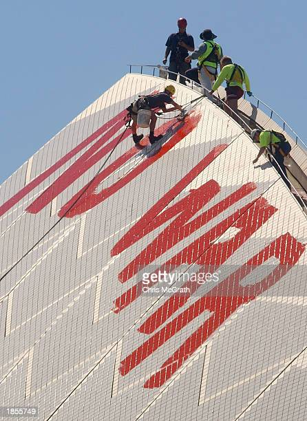 Sydney Opera House staff scrub off the 'No War' graffiti painted in blood red letters by anti war protesters on the tip of the tallest sail on March...