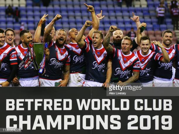 Sydney Roosters players celebrate victory with the trophy after the World Club Challenge match between Wigan Warriors and Sydney Roosters at DW...