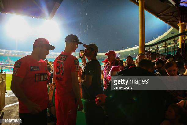 Sydney Sixers players sign autographs after play is stopped due to rain during the Big Bash League match between the Sydney Sixers and the Hobart...