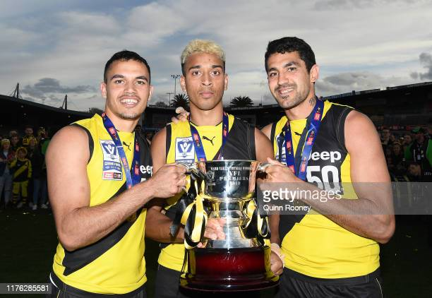 Sydney Stack, Derek Eggmolesse-Smith and Marlion Pickett of the Tigers poses with the Premiership Trophy during the VFL Grand Final match between the...