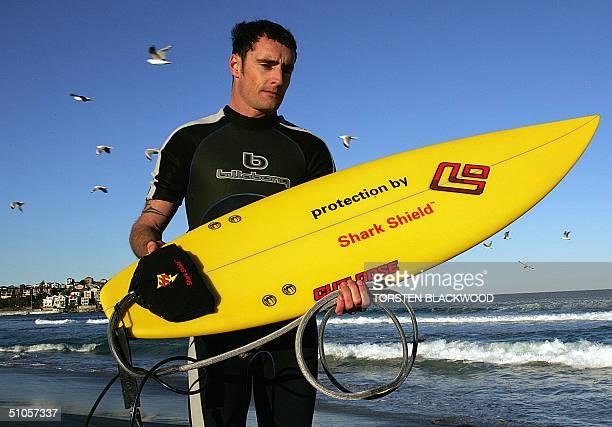 "Sydney surfer Michael James displays the new SeaChange ""Shark Shield"" shark deterrent system mounted near the tail of his surfboard on Sydney's Bondi..."