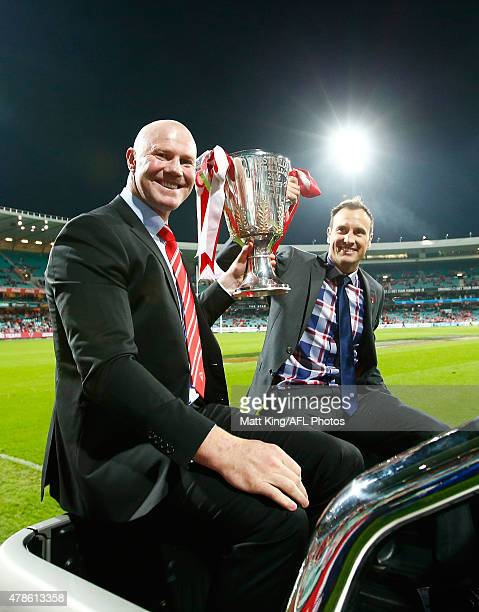 Sydney Swans premiership winning players Barry Hall and Jude Bolton take part in a lap of honour before the round 13 AFL match between the Sydney...