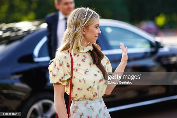 Sydney Sweeney wears a headband a floral print yellow ruffled tshirt a pale blue floral print skirt outside Miu Miu Club 2020 on June 29 2019 in...