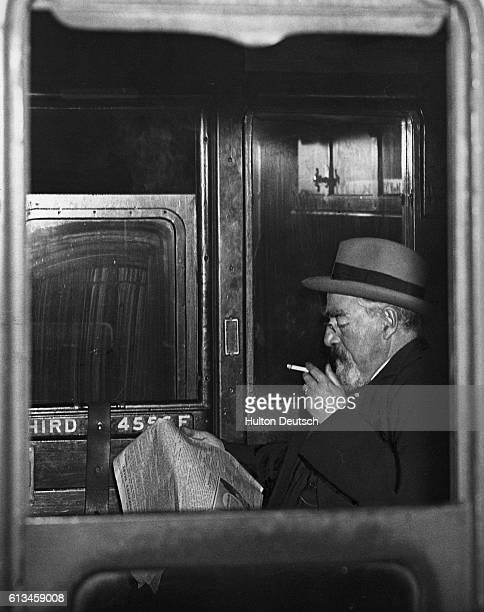 Sydney Webb the Labour politician social reformer and founder of the Fabian society smokes aboard a train
