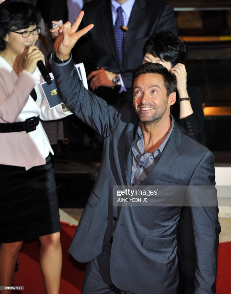 Sydney-born Hollywood star actor Hugh Jackman (R) waves to South Korean fans after a press conference to promote his film 'Les Miserables' at a hotel in Seoul on November 26, 2012. The film will open in December in South Korea.