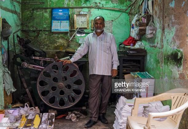 Syed Ahmed an Indian owner and operator of a letterpress printing machine poses in his shop in the old quarters of New Delhi on April 23 2018 There...