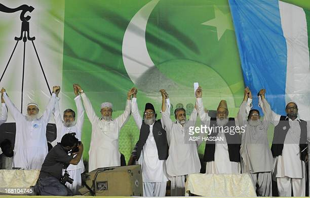Syed Munawar Hassan chief of JamateIslami raises hands with party leaders during an election campaign rally in Karachi on May 5 2013 A roadside bomb...
