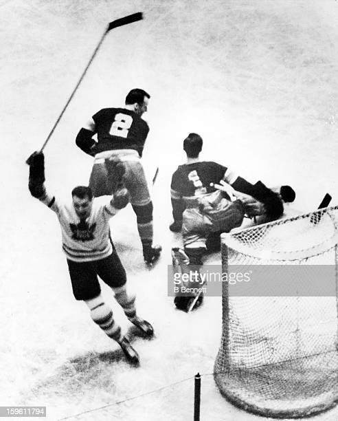 Syl Apps of the Toronto Maple Leafs scores past goalie Jim Henry and Art Coulter of the New York Rangers during Game 1 of the 1942 Semi-Finals on...