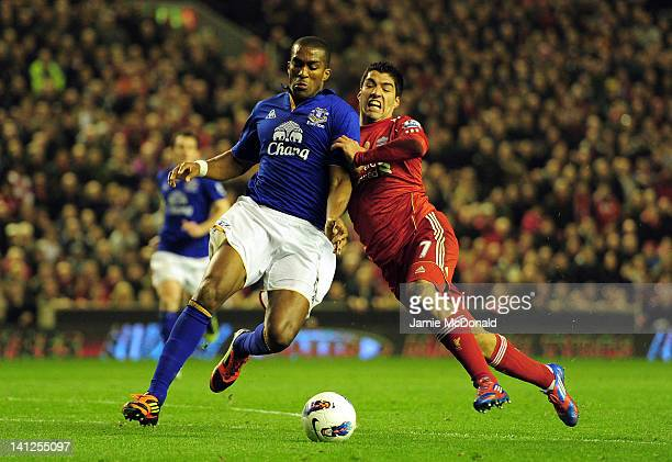Sylvain Distin of Everton and Luis Suarez of Liverpool battle for the ball during the Barclays Premier League match between Liverpool and Everton at...