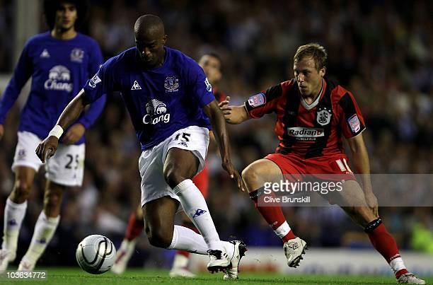 Sylvain Distin of Everton attempts to move away from Scott Arfield of Huddersfield Town during the Carling Cup second round match between Everton and...