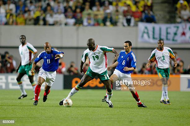 Sylvain Wiltord and Youri Djorkaeff of France combine to pressure Papa Bouba Diop of Senegal during the first half of the France v Senegal Group A...
