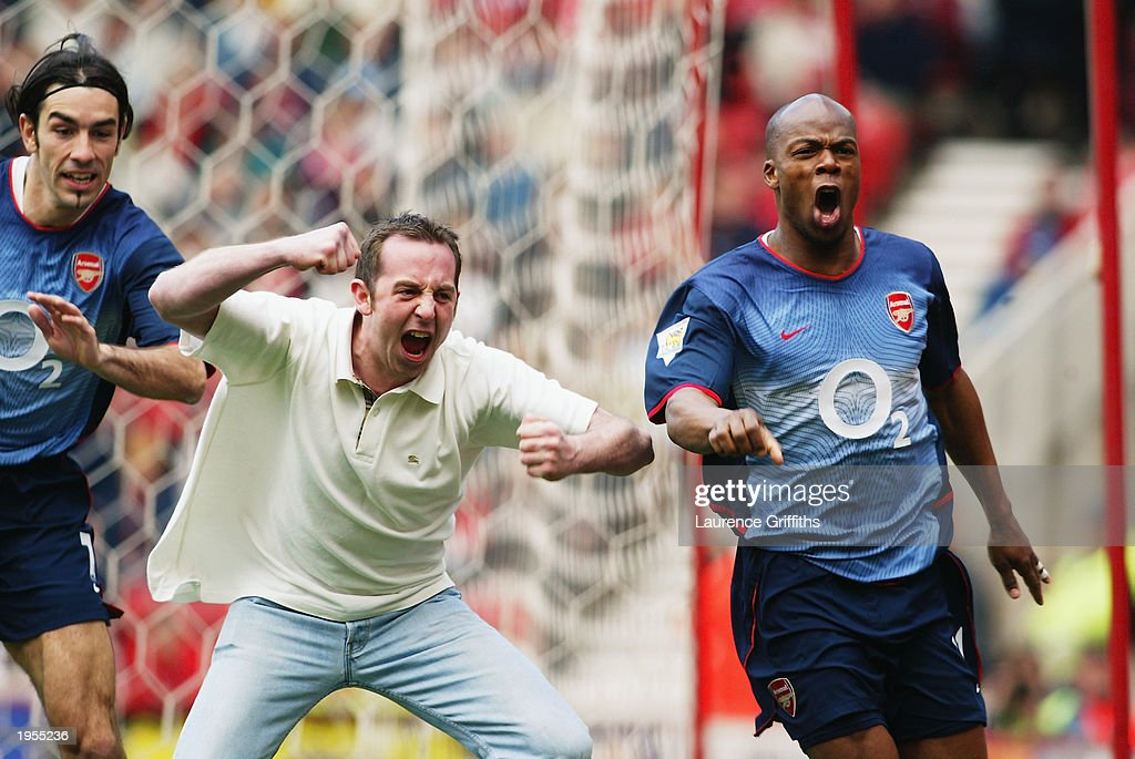 Sylvain Wiltord of Arsenal celebrates his goal with Robert Pires of Arsenal and an Arsenal supporter during the FA Barclaycard Premiership match between Middlesbrough and Arsenal held on April 19, 2003 at The Riverside Stadium in Middlesbrough, England. Arsenal won the match 2-0.