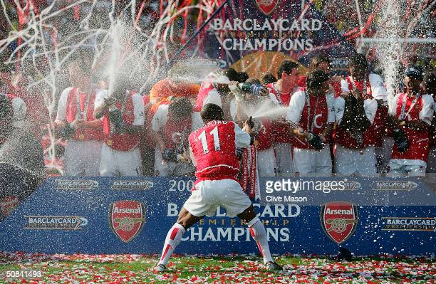 Sylvain Wiltord of Arsenal sprays his team mates with champagne as they celebrate winning the Premiership during the FA Barclaycard Premiership match...