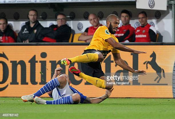 Sylvano Comvalius of Dresden is challenged by Marco Hoeger of Schalke 04 during the DFB Cup between SG Dynamo Dresden and FC Schalke 04 at...