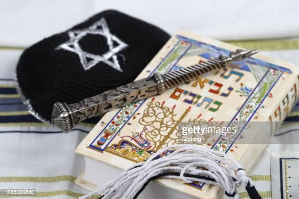 Sylver yad, black and white tzitzit, tallit, kippah and Torah. Jewish symbols. France.