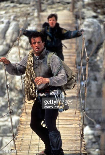 Sylvester Stallone and Janine Turner walking on a shakey wooden bridge in a scene from the film 'Cliffhanger' 1993
