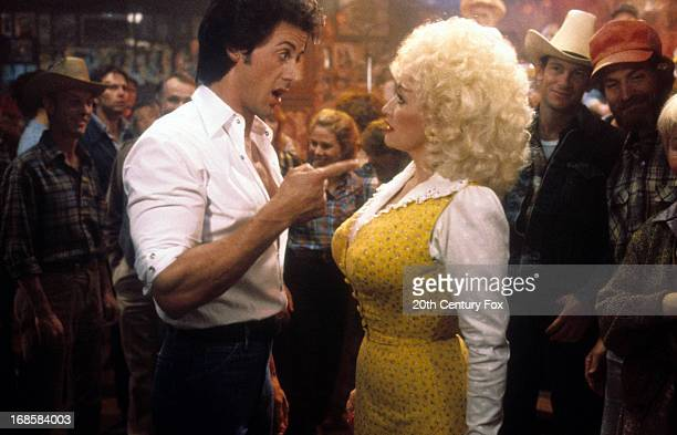 Sylvester Stallone points to Dolly Parton in a scene from the film 'Rhinestone' 1984