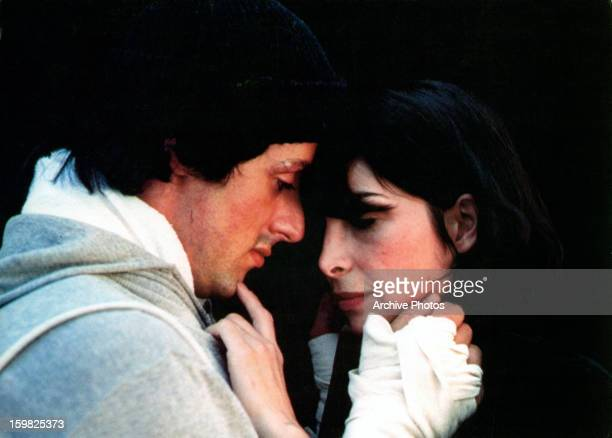 Sylvester Stallone sharing romantic moment with Talia Shire in a scene from the film 'Rocky', 1976.