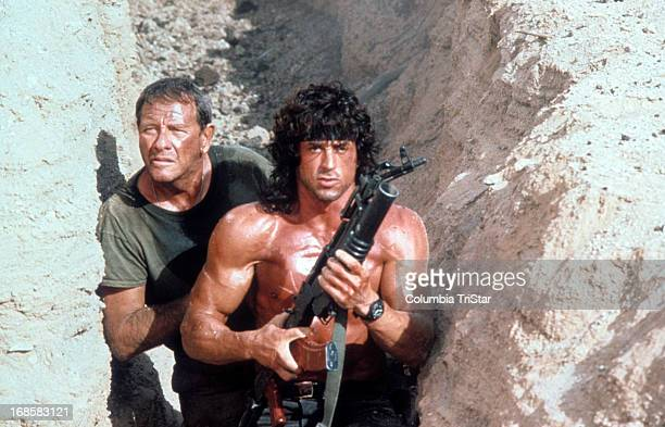 Sylvester Stallone walks through a trench with Richard Crenna in a scene from the film 'Rambo III' 1988