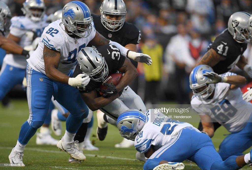 Sylvester Williams #92 and Quandre Diggs #28 of the Detroit Lions tackles Jalen Richard #30 of the Oakland Raiders during the first quarter of their NFL preseason football game at Oakland Alameda Coliseum on August 10, 2018 in Oakland, California.