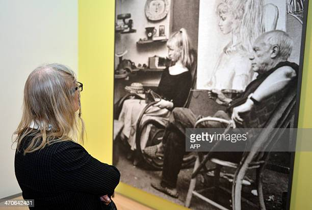 Sylvette David aka Lydia Corbett former model of Spanish artist Pablo Picasso looks at a photograph showing Spanish artist Pablo Picasso creating a...