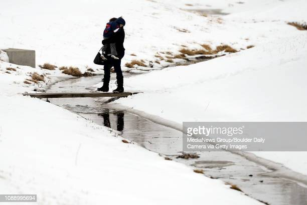 Sylvia De La Cruz of Lafayette carries her son Daniel Jiminez across a makeshift bridge on Tuesday Feb 26 while walking towards Alicia Sanchez...