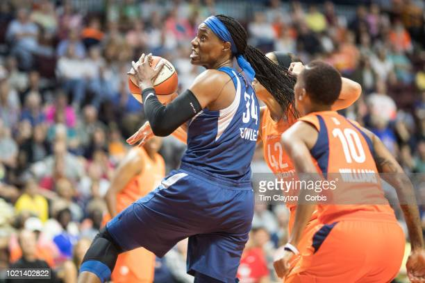 Sylvia Fowles of the Minnesota Lynx drives to the basket defended by Brionna Jones of the Connecticut Sun and Courtney Williams of the Connecticut...