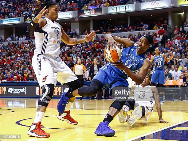 Sylvia Fowles of the Minnesota Lynx looks to pass the ball off as Erlana Larkins of the Indiana Fever guards at Bankers Life Fieldhouse on October 11...