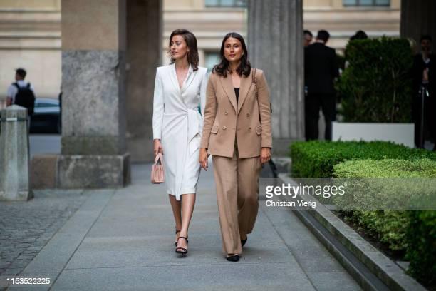 Sylvia Haghjoo is seen wearing white belted coat and Julia Haghjoo wearing brown suit outside Max Mara Resort 2020 on June 03, 2019 in Berlin,...