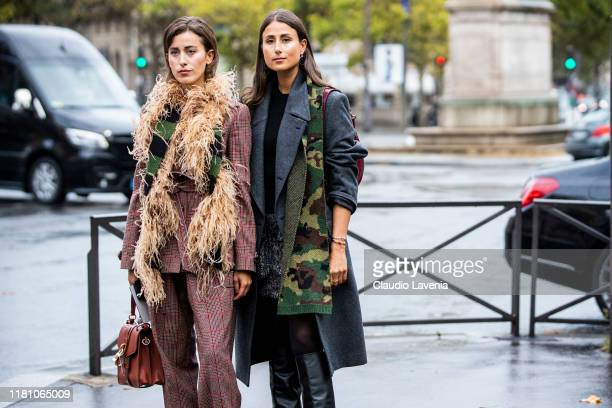 Sylvia Haghjoo , wearing a burgundy checked suit, fur scarf and brown bag, and Julia Haghjoo , wearing a grey coat, military print scarf and black...