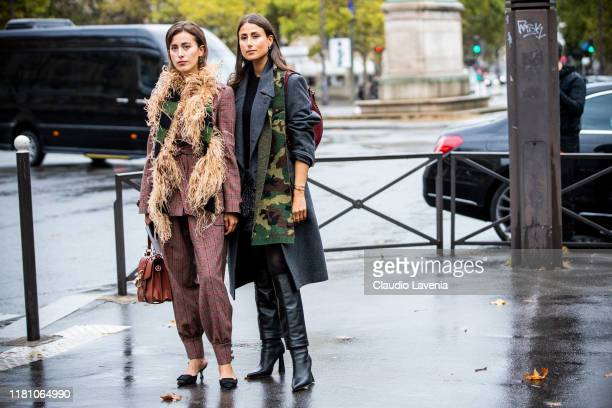 Sylvia Haghjoo , wearing a burgundy checked suit, fur scarf, black heels and brown bag, and Julia Haghjoo , wearing a grey coat, military print scarf...